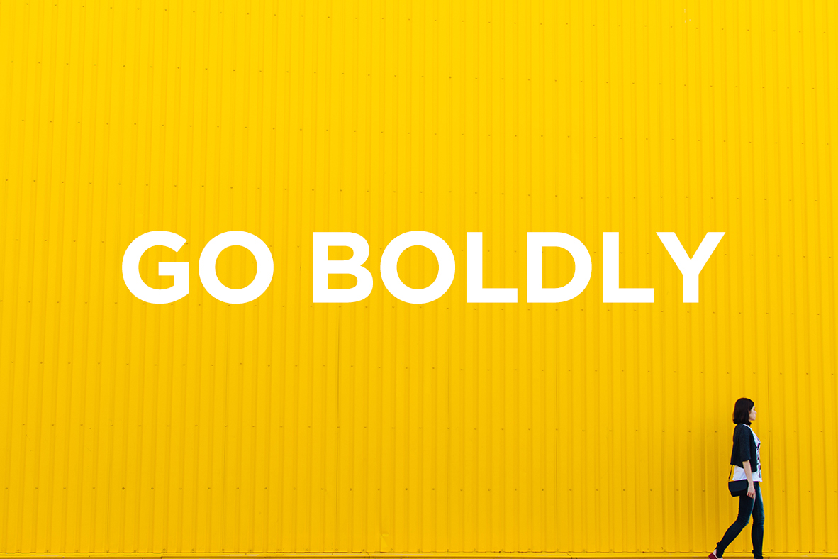 Go Boldly woman walking across yellow background