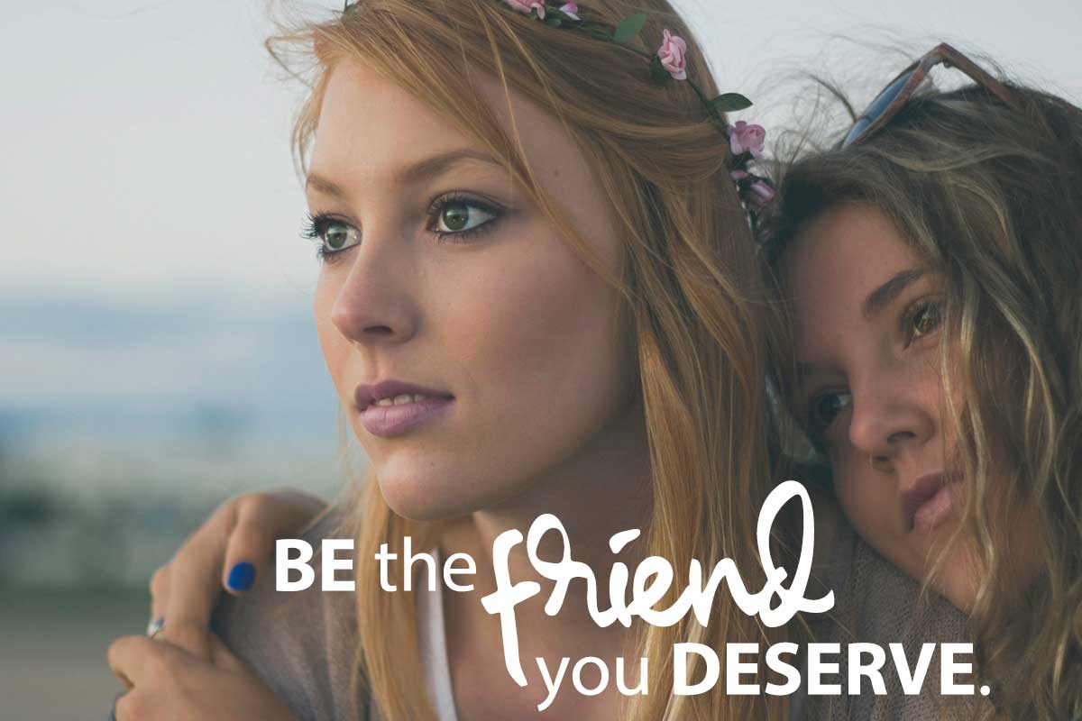 be the friend you deserve two woman looking out at the distance hold each other and looking peaceful