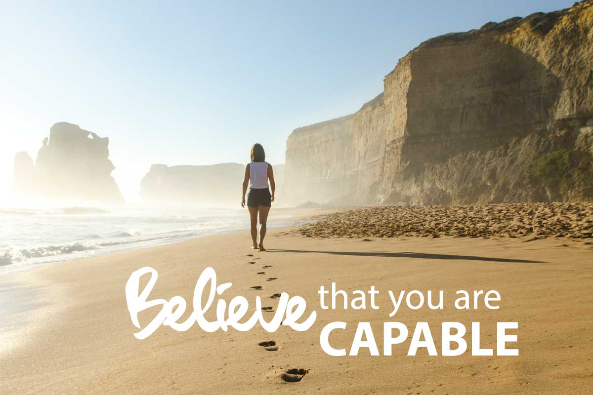 Believe that you are capable. Woman walking down beach leaving footprints in sand.