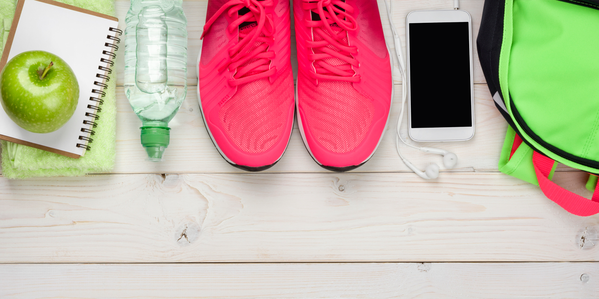 notebook with apple, water bottle, running shoes, phone, and back pack