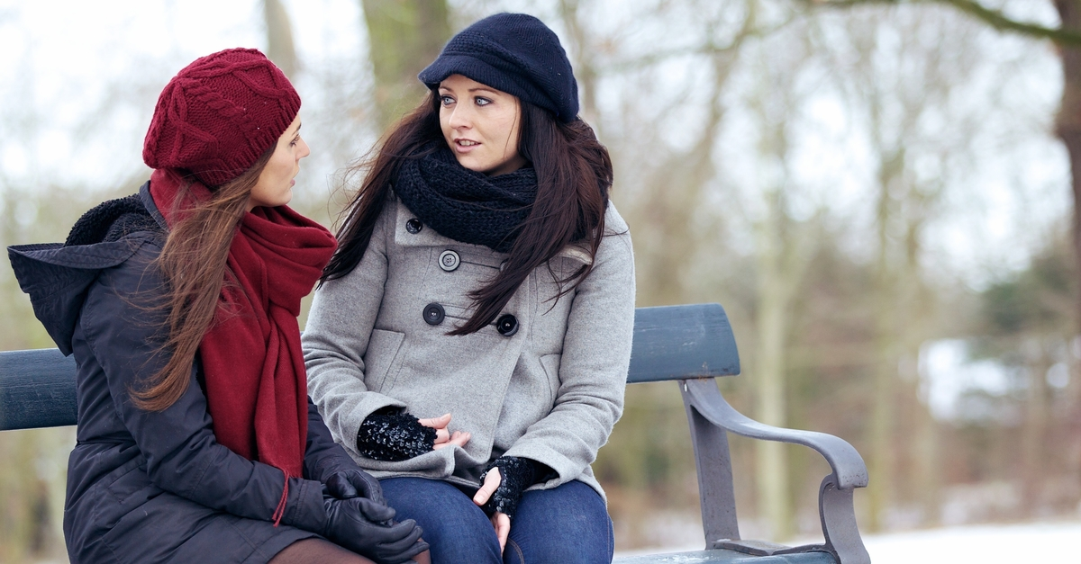 Two young women having an honest conversation on a park bench in winter.