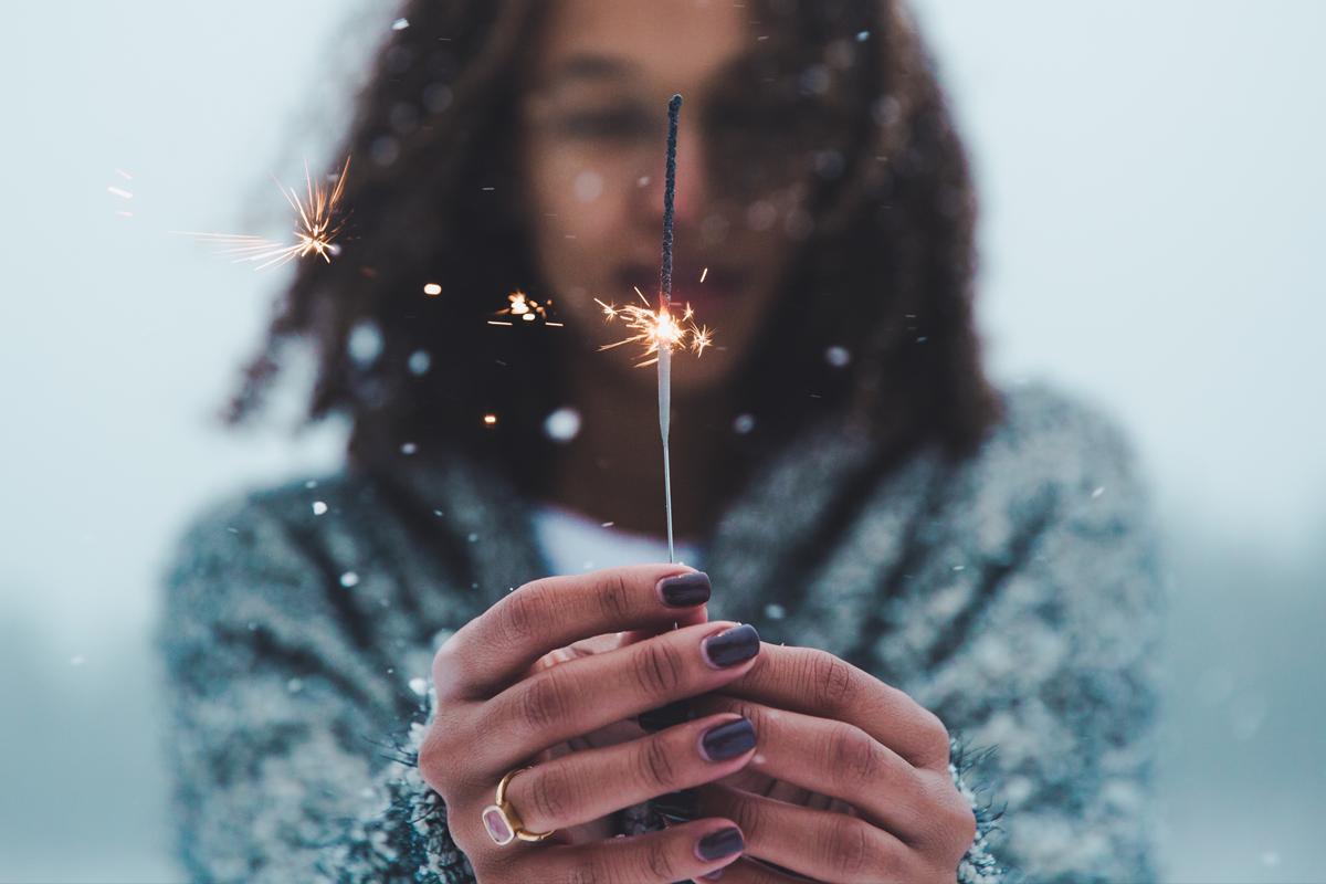 woman holding sparkler in snow