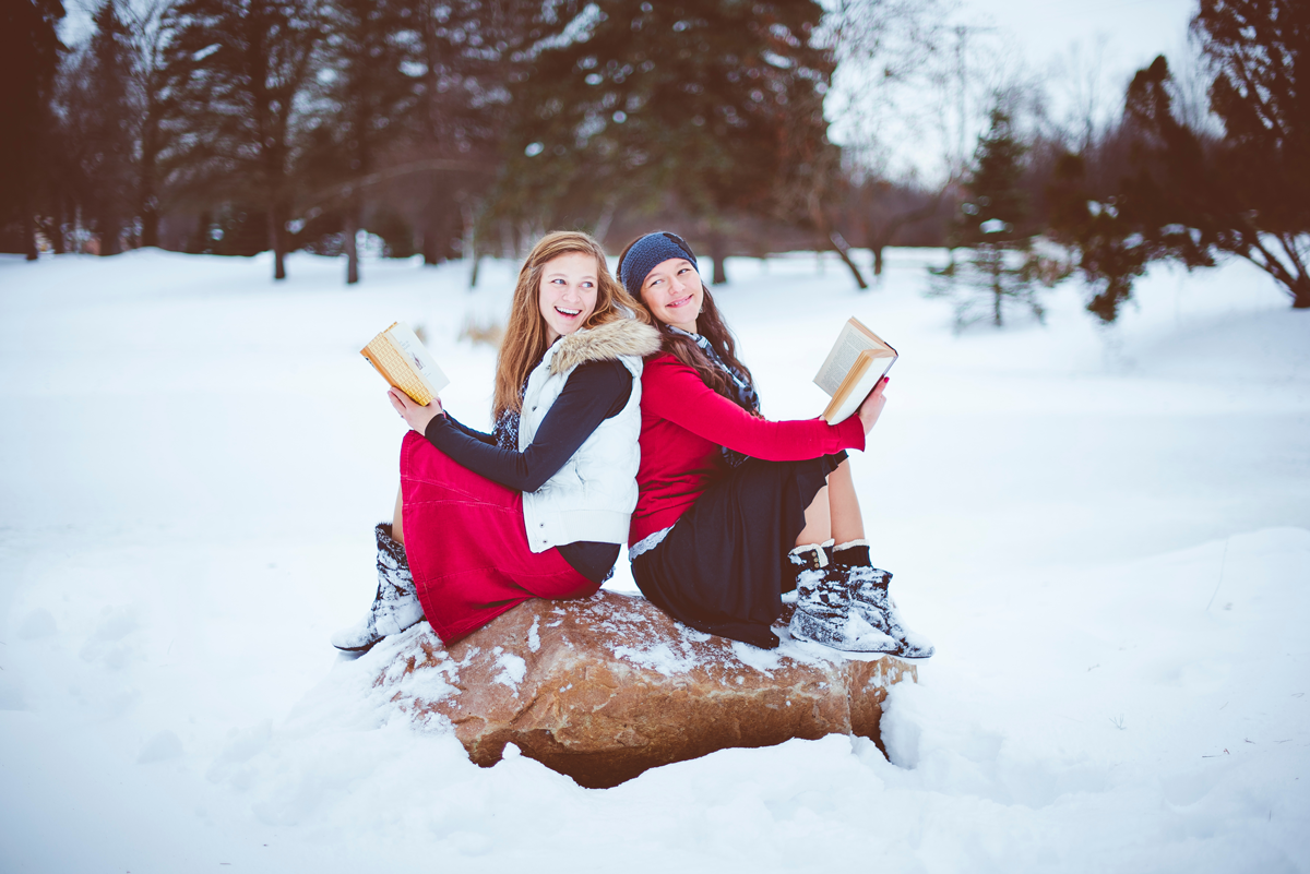 two girls outside in winter sitting on a snowy log with books