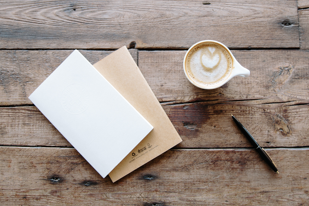 journal with coffee on a table