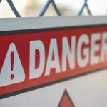 """warning sign that says """"danger"""" on a chain-link fence"""