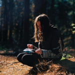 Young woman sitting in woods journaling as a strategy for coping after intimate partner violence.