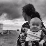 Woman with child in arms looking back at a trailer.