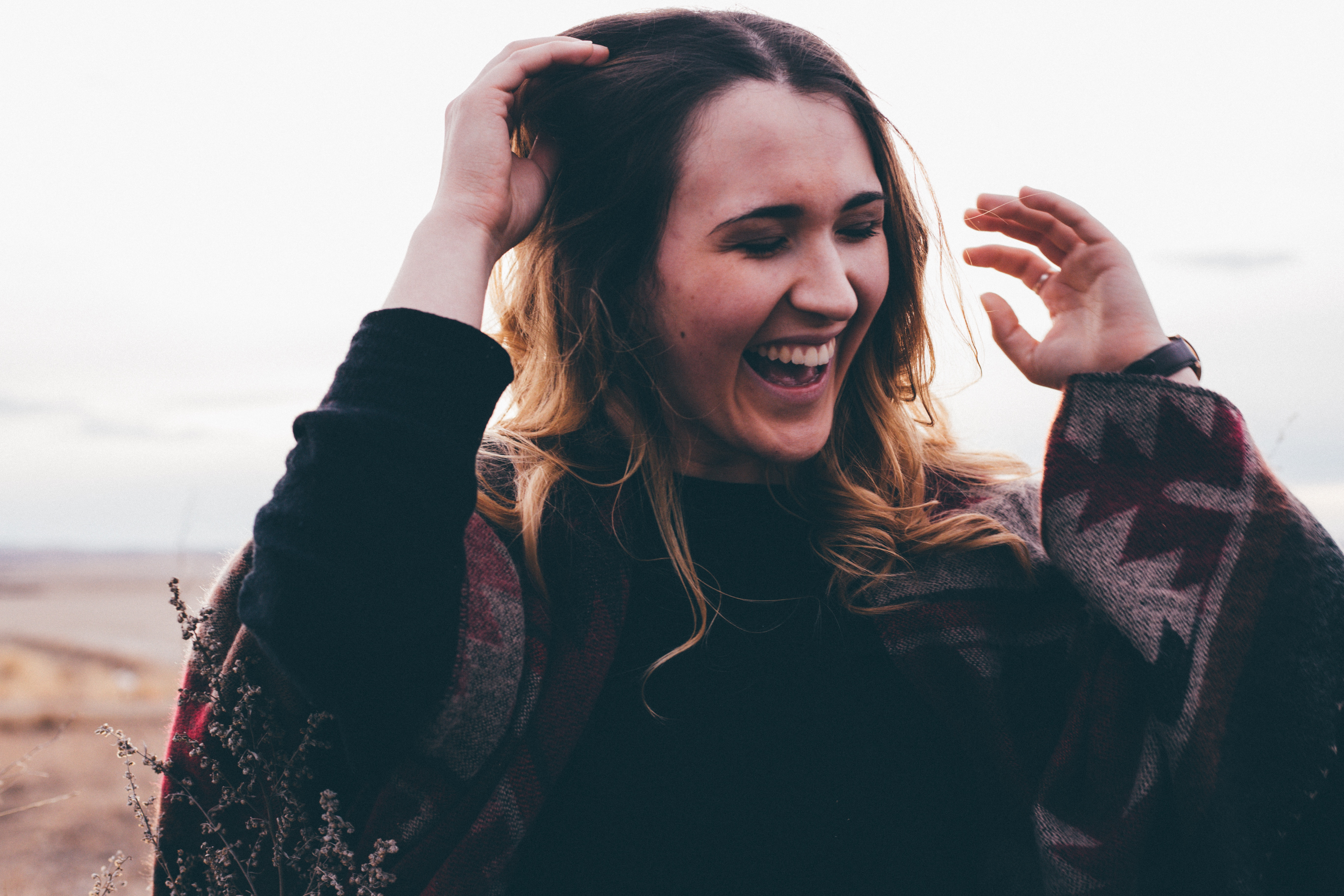 Woman wearing sweater laughs, one hand on hair, one in air; gratitude for women's health care advances