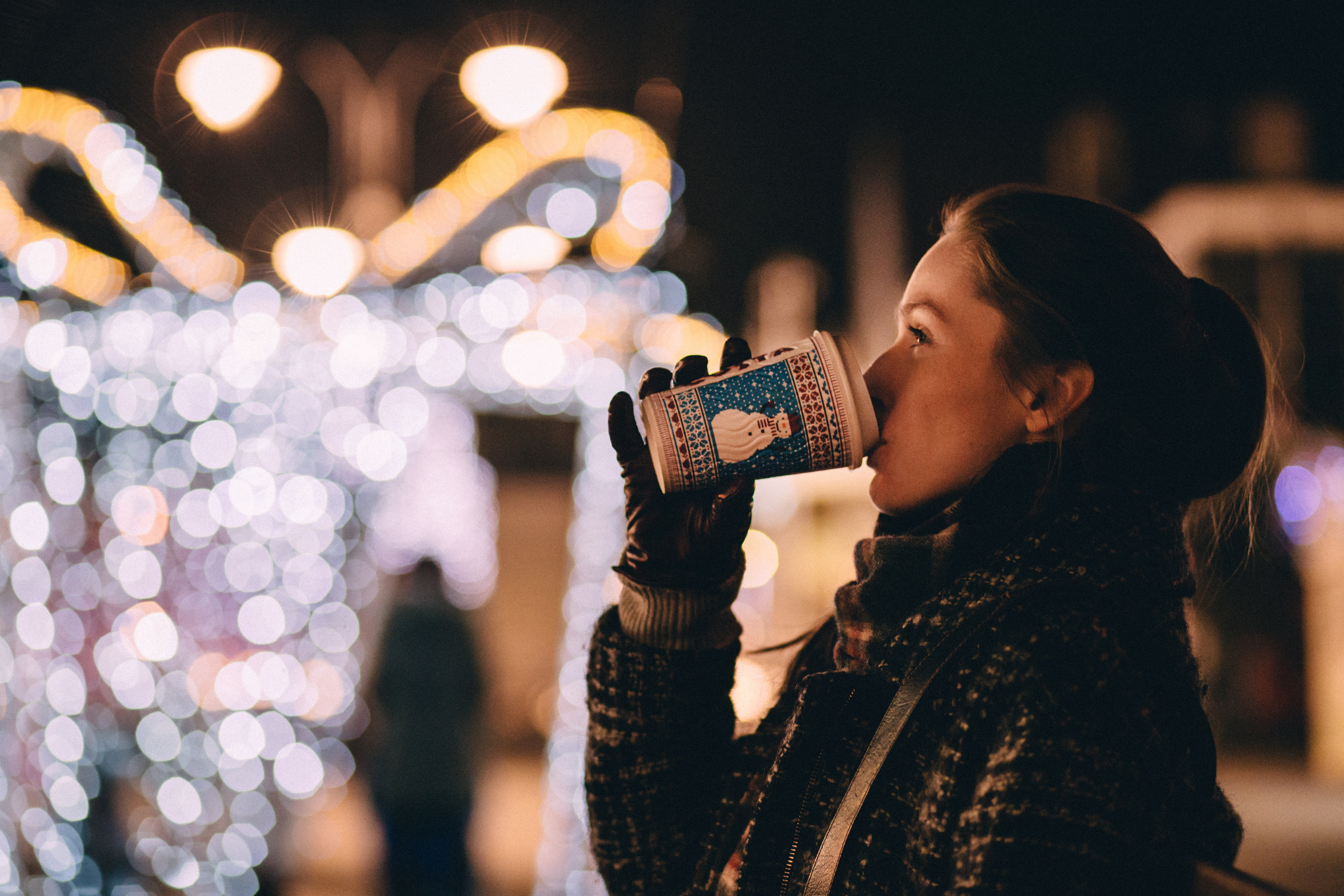 Woman admires christmas lights while sipping a hot beverage.