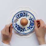 Top Down Photo of Woman's Hands Around an Egg on a blue and white saucer