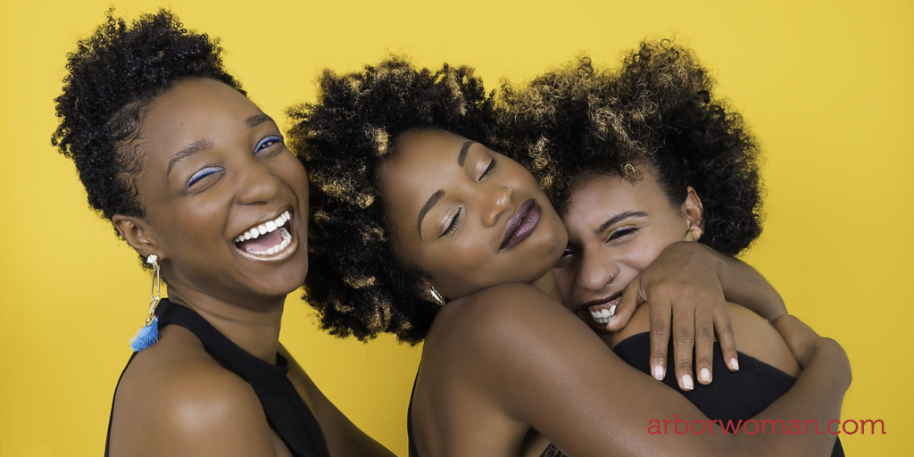 Three women joyfully embrace each other in front of a bright yellow background
